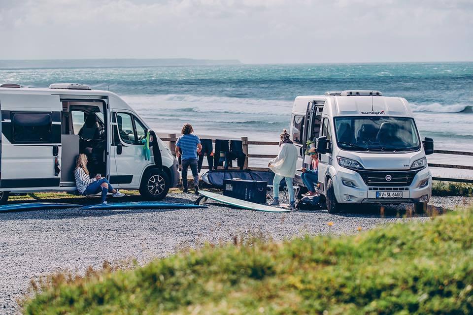 Área de autocaravana en Valencia en la playa con gente joven preparándose para viajar