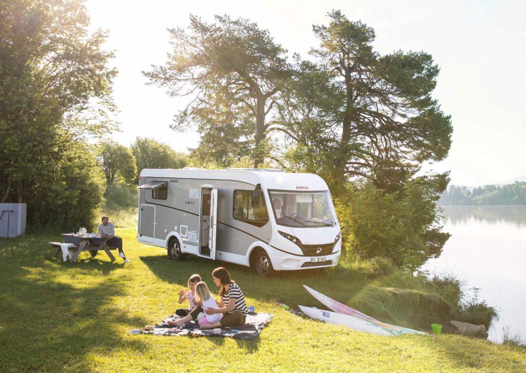 Autocaravana de lujo al lado de un lago con una familia sentada en el césped.